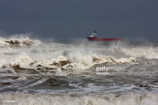 A tanker is waiting to enter the harbor on a rough sea