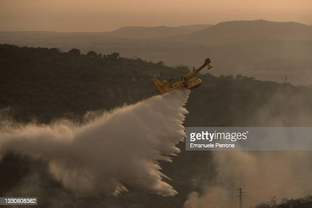 Tanker plane drops water on a blaze that has destroyed thousands of hectares of land on July 25, 2021 in the province of Oristano in Sardinia, Italy....