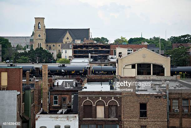 Tanker rail cars bearing UN 1267 petroleum crude oil class 3 hazardous materials placards travel on an elevated railway through Aurora Illinois US on...