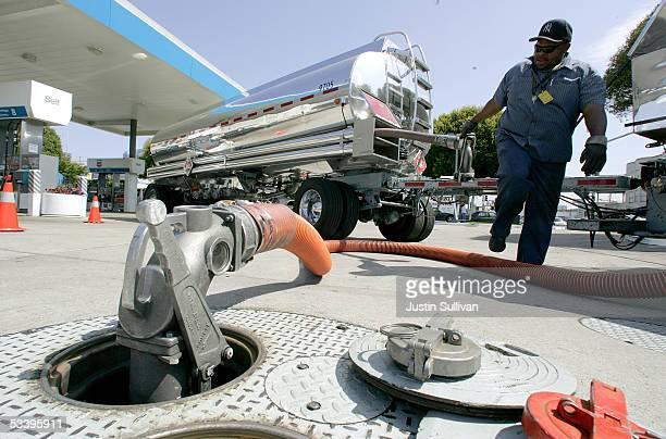 Tanker truck driver Bill Moore pumps gasoline into a ground tank at a Chevron service station during a delivery August 16 2005 in San Francisco...