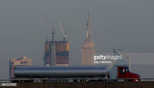 A tanker truck drives on the New Jersey Turnpike in front of Hudson Yards and the Empire State Building in New York City on September 24 as seen from...