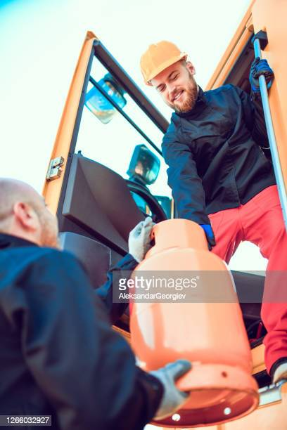 tanker truck team lifting gas cylinder to load it on truck - butane stock pictures, royalty-free photos & images