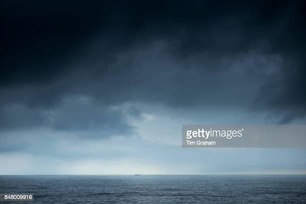 Tanker under dark looming grey storm clouds in The Bay of Biscay north of Santander in the Atlantic Ocean Spain