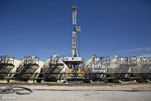 Tanks containing drilling fluid sit in a row near a Nabors Industries Ltd rig drilling for Chevron Corp in the Permian Basin near Midland Texas US on...