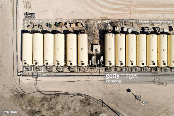 Tanks containing drilling fluid sit in a row near a Nabors Industries Ltd rig drilling for Chevron Corp in the Permian Basin in this aerial...