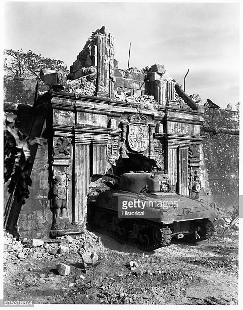 Tanks enter through the historic gate of old Fort Santiago which was damaged by shells when troops stormed Manila