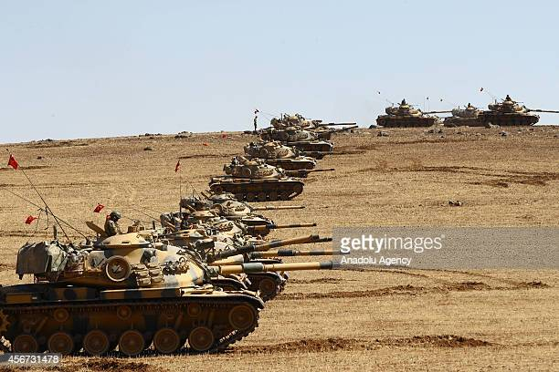 Tanks of Turkish Armed Forces are seen on the hills at the Turkey Syria borderline in the Suruc district of Sanliurfa Turkey as the clashes between...