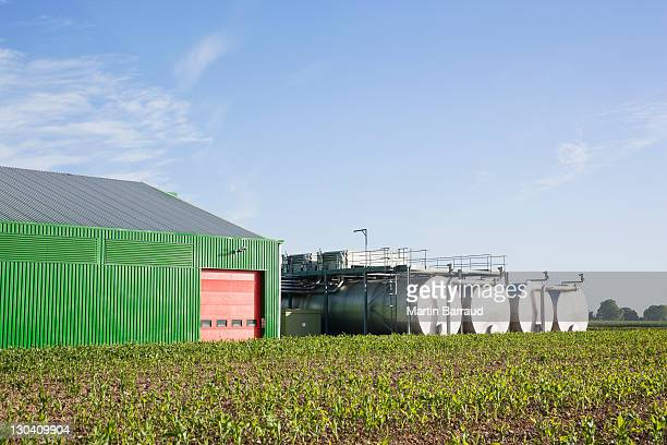 tanks outside warehouse in rural landscape - storage tank stock pictures, royalty-free photos & images
