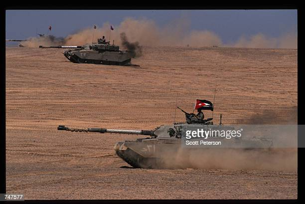 Tanks race along the sand May 31 1997 in Qatraneh Jordan The forces are taking part in military exercises called 'Infinite Moonlight' which will...