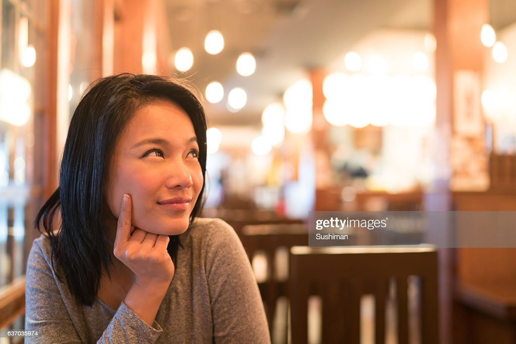 Tanned Asian girl looking upward to copy space at restaurant : Stock-Foto
