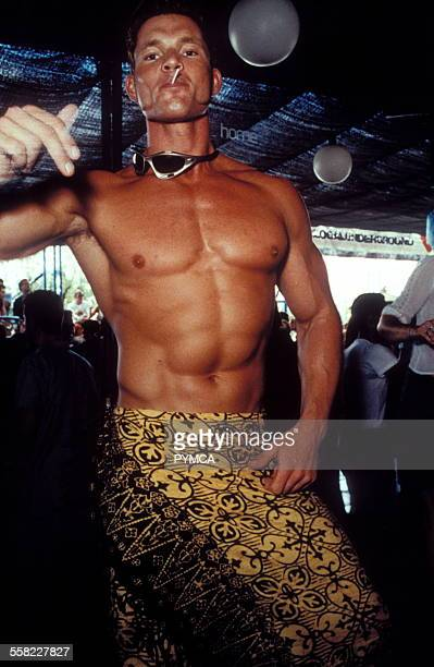 A tanned man shows off his six pack and new skirt in Ibiza 1999