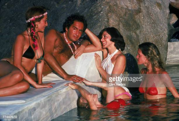 A tanned man surrounded by young women in bikinis by the pool at Warren Avis's villa in Acapulco Mexico January 1978