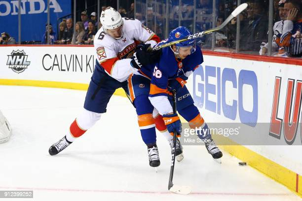 Tanner Fritz of the New York Islanders and Alexander Petrovic of the Florida Panthers engage in a physical puck battle behind the net during the...
