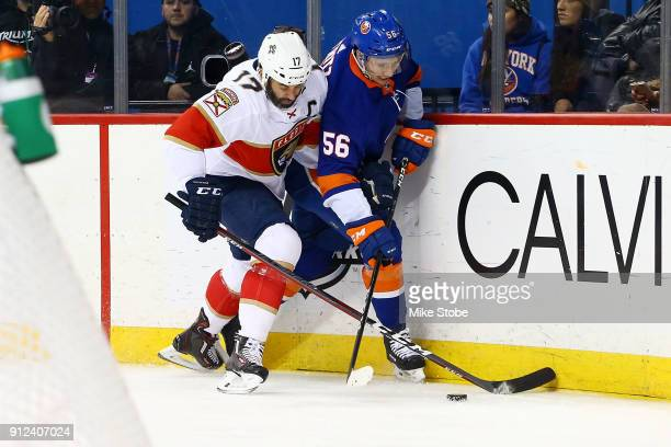 Tanner Fritz of the New York Islanders and Derek MacKenzie of the Florida Panthers battle for the puck along the boards during the second period at...