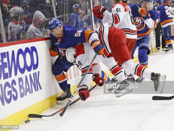 Tanner Fritz of the New York Islanders and Sebastian Aho of the Carolina Hurricanes battle along the boards during the second period at the Barclays...