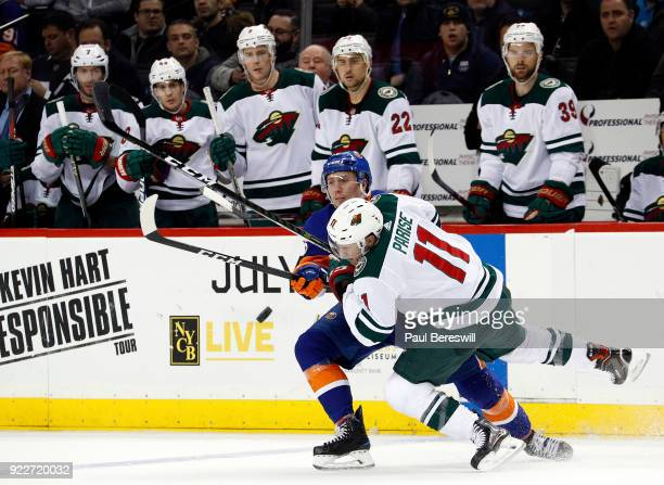 Tanner Fritz of the New York Islanders and Zach Parise of the Minnesota Wild battle for the puck in an NHL hockey game at Barclays Center on February...