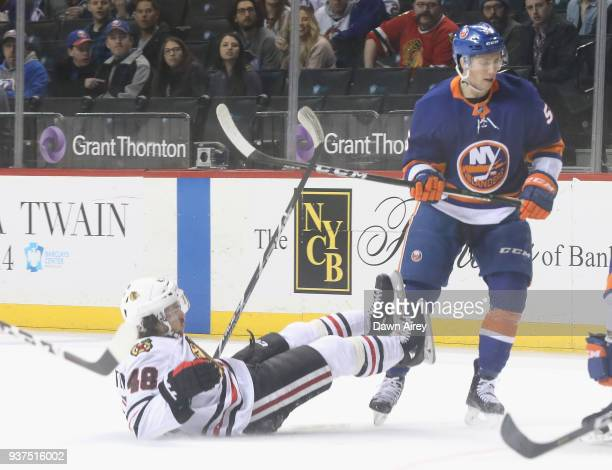 Tanner Fritz of the New York Islanders checks Vinnie Hinostroza of the Chicago Blackhawks during the first period at the Barclays Center on March 24...