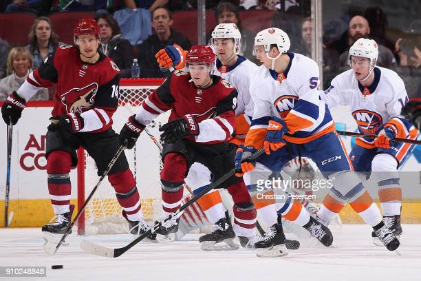 Tanner Fritz of the New York Islanders controls the puck ahead of Clayton Keller of the Arizona Coyotes during the first period of the NHL game at...