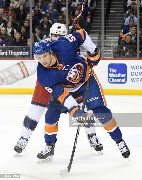 Tanner Fritz of the New York Islanders skates is checked from behind by David Savard of the Columbus Blue Jackets during the third period at Barclays...