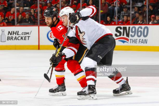 Tanner Glass of the Calgary Flames and Christian Fischer of the Arizona Coyotes battle for position in an NHL game on April 3 2018 at the Scotiabank...