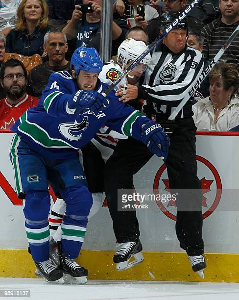 Tanner Glass of the Vancouver Canucks checks Patrick Kane of the Chicago Blackhawks into Linesmen Jay Sharrers in Game Four of the Western Conference...