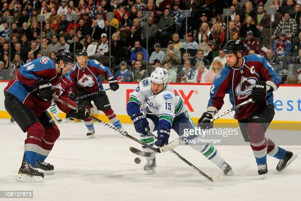Tanner Glass of the Vancouver Canucks tries to control the puck between Tomas Fleischmann and Adam Foote of the Colorado Avalanche at the Pepsi...
