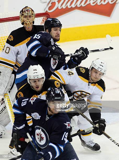 Tanner Glass of the Winnipeg Jets puts pressure on Dennis Seidenberg of the Boston Bruins in NHL action at the MTS Centre on December 6 2011 in...
