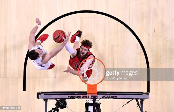 Tanner Groves of the Eastern Washington Eagles puts the ball up against Mitch Lightfoot of the Kansas Jayhawks in the first round of the 2021 NCAA...