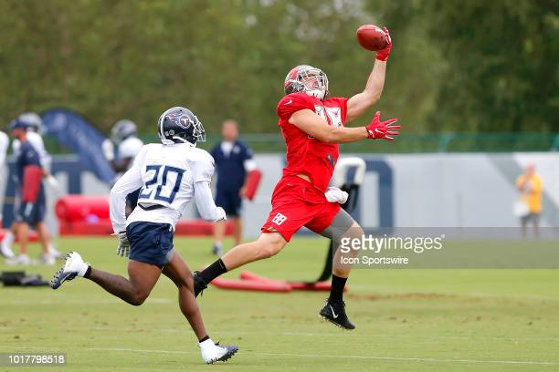 Tanner Hudson of the Bucs makes a one handed catch as Demontre Hurst of the Titans looks on during the joint training camp work out between the Tampa...