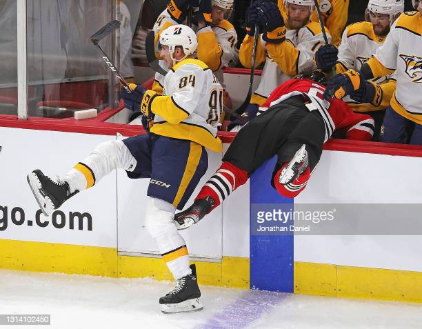 Tanner Jeannot of the Nashville Predators dumps Duncan Keith of the Chicago Blackhawks into the Predators bench at the United Center on April 23,...