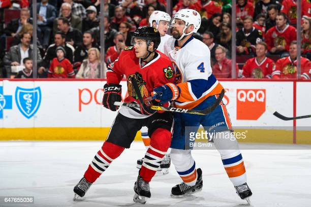 Tanner Kero of the Chicago Blackhawks and Dennis Seidenberg of the New York Islanders watch for the puck in the first period at the United Center on...