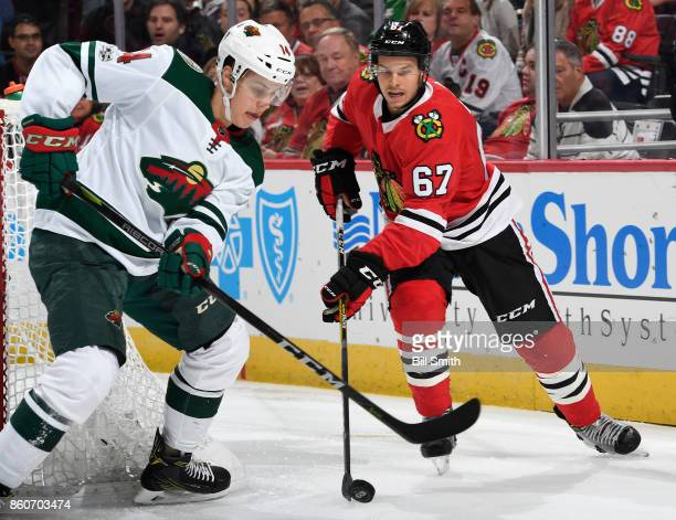 Tanner Kero of the Chicago Blackhawks grabs the puck against Joel Eriksson Ek of the Minnesota Wild in the first period at the United Center on...