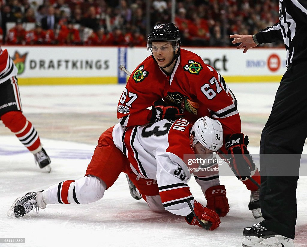 Tanner Kero #67 of the Chicago Blackhawks lands on top of Derek Ryan #33 of the Carolina Hurricanes after a face-off at the United Center on January 6, 2017 in Chicago, Illinois. The Blackhawks defeated the Hurricanes 2-1.