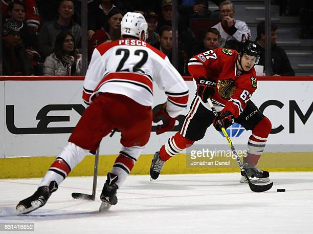 Tanner Kero of the Chicago Blackhawks looks to pass against Brett Pesce of the Carolina Hurricanes at the United Center on January 6 2017 in Chicago...