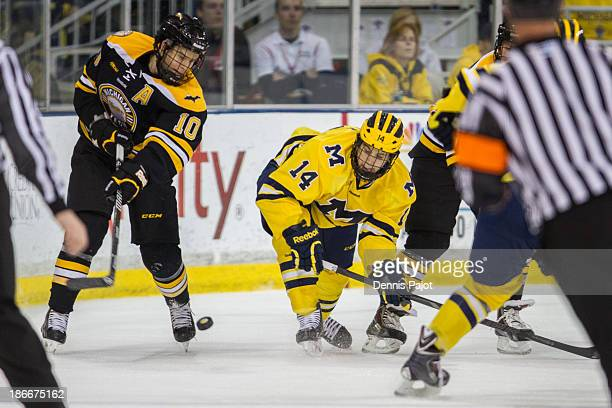 Tanner Kero of the Michigan Tech Huskies battles for the puck against Tyler Motte of the Michigan Wolverines on November 2 2013 at Yost Ice Arena in...