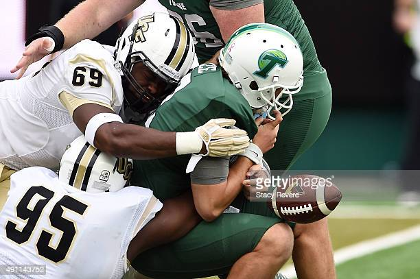 Tanner Lee of the Tulane Green Wave loses the ball after being sacked by Thomas Niles and Jamiyus Pittman of the UCF Knights during the first quarter...