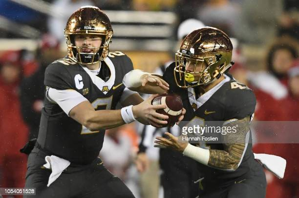 Tanner Morgan of the Minnesota Golden Gophers fakes a hand off of the ball to teammate Shannon Brooks during the first quarter of the game on October...