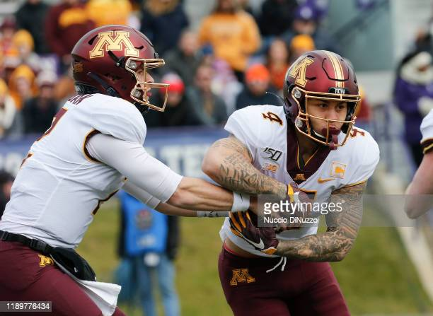 Tanner Morgan of the Minnesota Golden Gophers hands the ball off to Shannon Brooks during the game against the Northwestern Wildcats at Ryan Field on...
