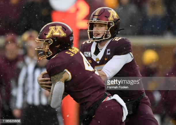 Tanner Morgan of the Minnesota Golden Gophers hands the ball to teammate Shannon Brooks during the second quarter of the game at TCF Bank Stadium on...