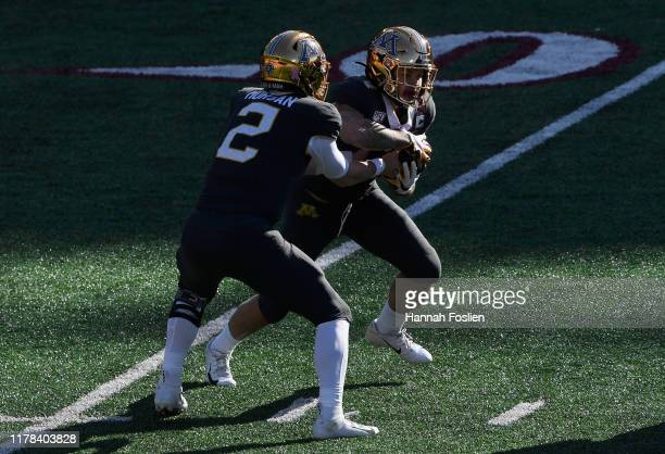 Tanner Morgan of the Minnesota Gophers hands the ball to teammate Shannon Brooks against the Maryland Terrapins during the first quarter of the game...