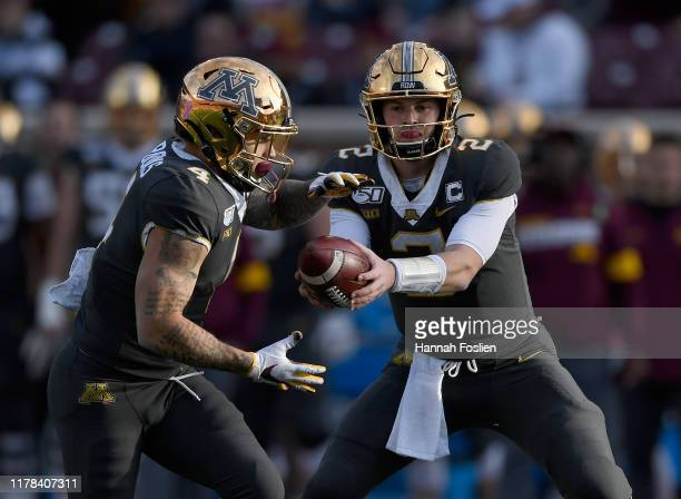 Tanner Morgan of the Minnesota Gophers hands the ball to teammate Shannon Brooks against the Maryland Terrapins during the third quarter of the game...
