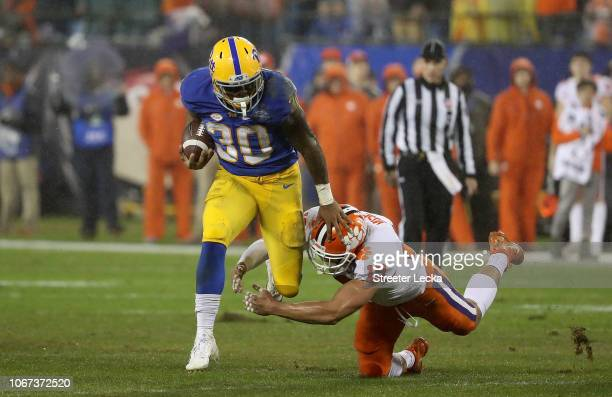 Tanner Muse of the Clemson Tigers tries to stop Qadree Ollison of the Pittsburgh Panthers during their game at Bank of America Stadium on December 1...