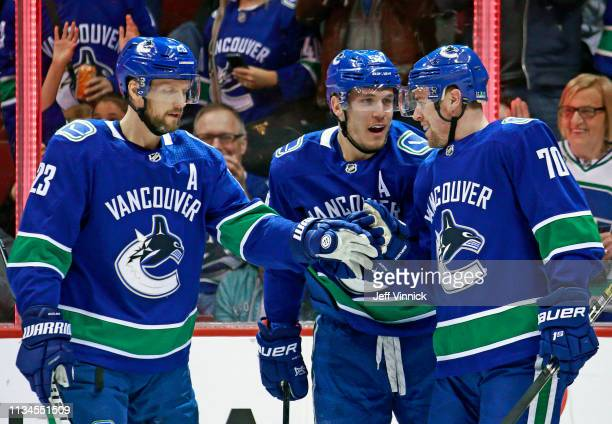 Tanner Pearson of the Vancouver Canucks is congratulated by teammates Alexander Edler and Bo Horvat after scoring during their NHL game at Rogers...