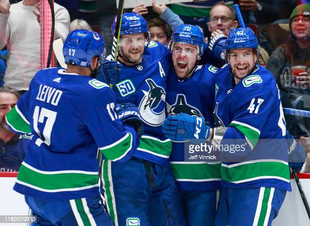 Tanner Pearson of the Vancouver Canucks is congratulated by teammates Josh Leivo, Sven Baertschi, and Alexander Edler after scoring during their NHL...