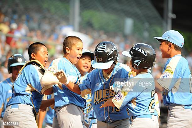 Tanner Tokunaga of the Waipio Little League team is greeted by teammates after hitting a home run during the World Series Championship game against...