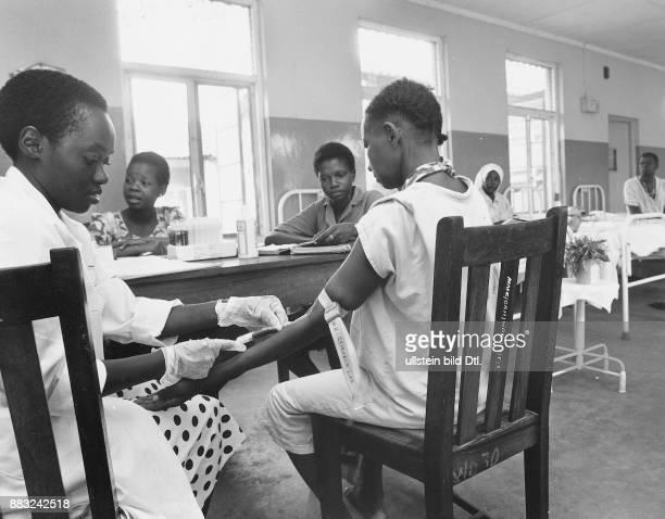 Tansania Im 'OceanBoulevardKrankenhaus' von Daressalaam wird bei einer Patientin ein AidsTest durchgeführt Eine Krankenhausangestellte nimmt ihr mit...