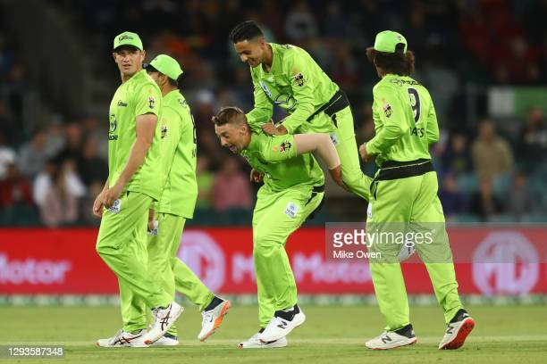 Tanveer Sangha of the Thunder jumps on the back of Daniel Sams of the Thunder after dismissing Nicholas Pooran of the Stars during the Big Bash...