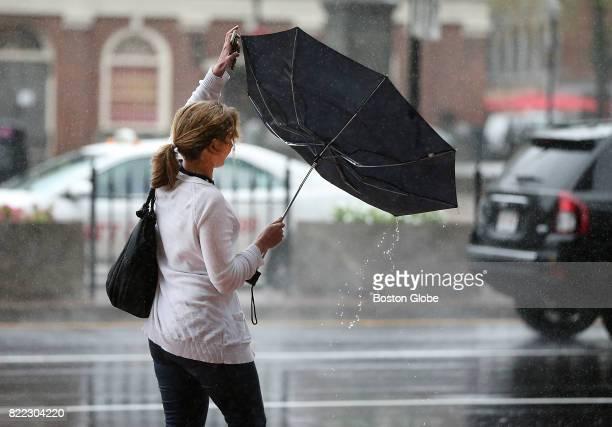 Tanya Inwalt of Boston struggles with her umbrella as she walks up Merrimac Street in South Boston on Jul 24 2017