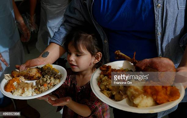 Tanya Le Flore with daughter Olia Le Flore of Long Beach standing in line for his Thanksgiving meal The United American Indian Involvement group is...