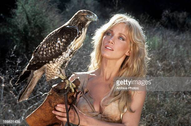 Tanya Roberts holding a perch with a bird on it in a scene from the film 'Sheena Queen of the Jungle' 1984